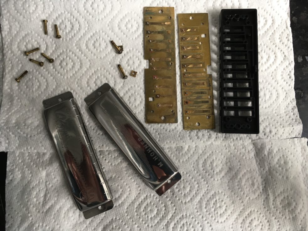 A Hohner Special 20's component parts played out on kitchen roll